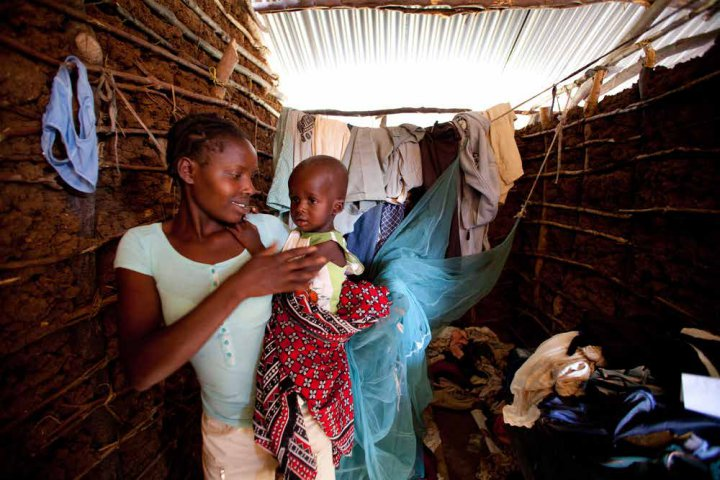 Family in Kenya with a bednet. ©PATH/Eric Becker.