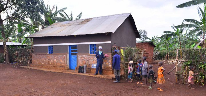 A malaria spray operator in a village in Rwanda talking to household members before spraying their home. ©Innovative Vector Control Consortium