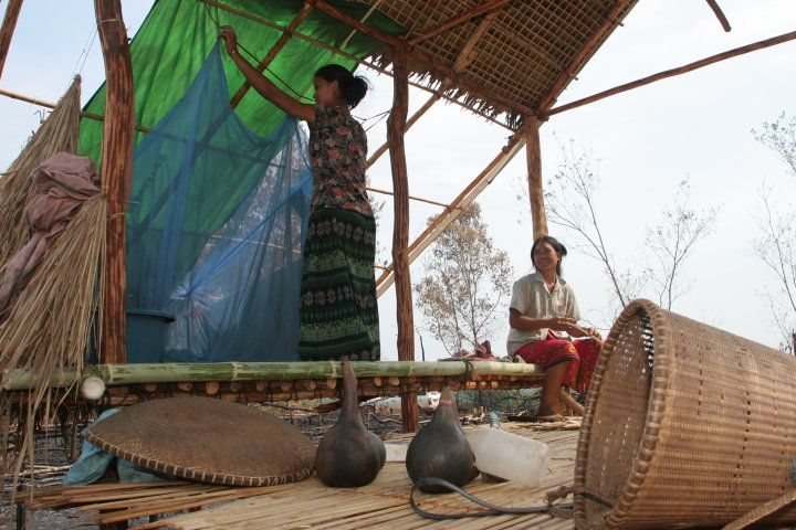 © WHO, S. Hollyman. A woman hangs a mosquito net in the temporary dwelling in the fields (champka) that she and her husband are clearing to farm, Cambodia.